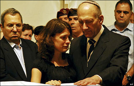 Israeli Defence Minister Ehud Barak (L) and Prime Minister Ehud Olmert (R) beside Karnit Goldwasser, the wife Ehud Goldwasser, praying over his coffin