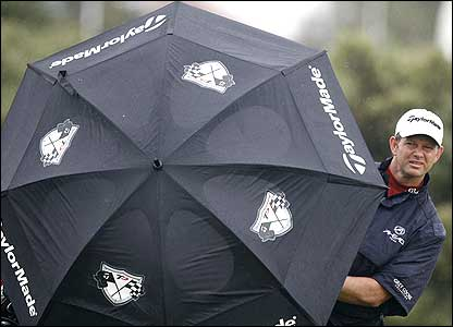 Retief Goosen looks out from behind his umbrella during the first round