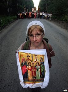 A woman holds an icon of Russian Tsar Nicholas II and his family during a religious procession