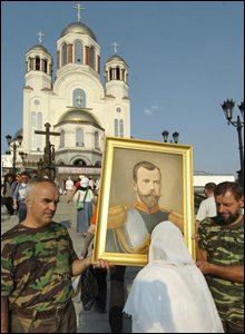 A woman kisses a portrait of Russian Tsar Nicholas II in front of the Church On The Blood in Yekaterinburg