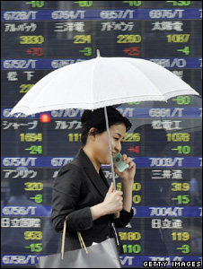 Woman under an umbrella walks past screen showing share prices (Getty Images)