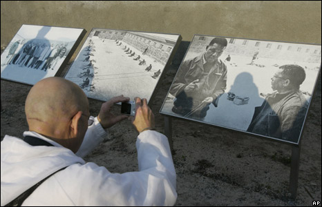 A man takes a photo of a historical photo of Nelson Mandela on Robben Island, South Africa