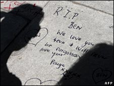 Teenagers gather to leave messages at the scene of the murder of Ben Kinsella