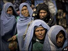 Afghan women wait for food rations distributed by an international aid group in Kabul (file image)