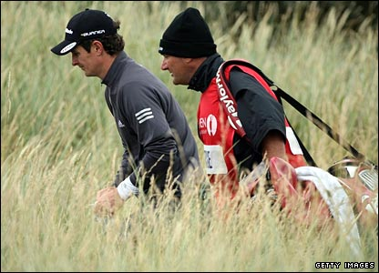 Justin Rose and his caddie wade through the rough at Royal Brikdale during the third round