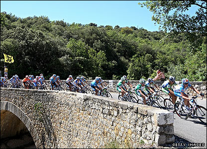 With the hot sun beating down on their backs the riders pass over an ancient bridge