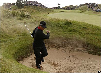 Overnight leader KJ Choi turns his face away as the sand flies up following a third round bunker shot