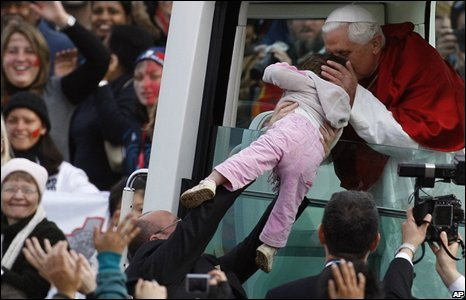 Pope Benedict kisses a baby while riding in his popemobile