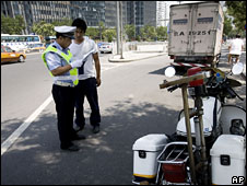 A traffic policeman carries out a check on a motorist, Beijing, 20 July