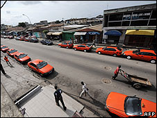 "Taxis line a street in the Treichville quarter of Abidjan on July 17, 2008. Tens of thousands of people in Ivory Coast""s capital Abidjan were forced to walk to work as taxi and minibus drivers began"