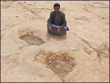 Local councillor Abdul Aziz poses next to some sauropod prints