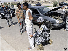 Iraqi police search a motorist in Baghdad on 21 July