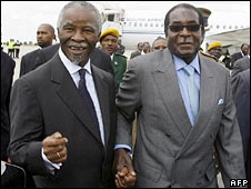 Thabo Mbeki (left) is greeted by Robert Mugabe at Harare's international airport, 21 July 2008