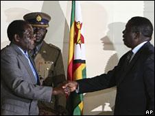 Robert Mugabe (L) and Morgan Tsvangirai shake hands at the signing of a deal in Harare, 21 July 2008