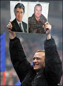 Serbian nationalist holds up pictures of Radovan Karadzic (left) and Ratko Mladic