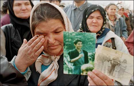 Bosnian mother showing pictures of two sons killed at Srebrenica