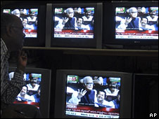 A man in India watches the parliamentary debate leading up to the vote of confidence on television