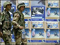 جنديان عراقيان يسيران بمحاذاة ملصق إعلان انتخابي