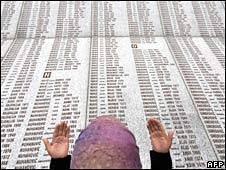 A Bosniak woman prays at a memorial wall near Srebrenica with the names of the victims of the massacre