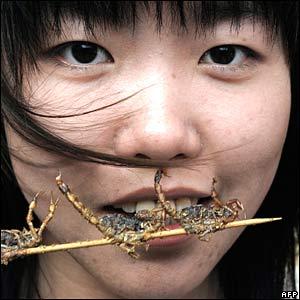 A woman eats scorpions on a stick in Beijing