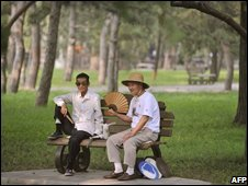 Two people chat in Ritan park, one of three designated protest venues