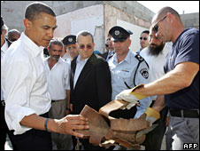 Barack Obama (left) inspects the remains of a Qassam rocket fired from the Gaza Strip into the southern Israeli town of Sderot, 23 July 2008
