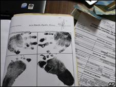 Documents showing the finger and foot prints of a baby up for adoption on a desk at the Attorney General's office in Guatemala City