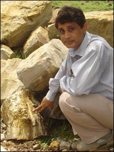 Geologist Syed Raza Imam Rizvi points to a fossil lying by the roadside