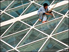 A Chinese worker puts the finishing touches to the Olympics stadium known as the Bird's Nest in Beijing on Wednesday