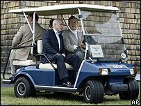 McCain y Bush padre llegan en un carro de golf a una rueda de prensa en Maine