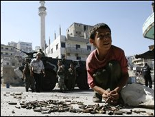 Boy collects spent cartridges after earlier round of Tripoli fighting