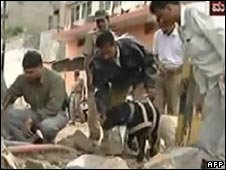 A TV grab of security officials using a sniffer dog to search debris at the site of a blast in Bangalore