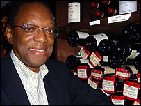 Alvin Hall stands by a collection of wines in the 21 Club in New York