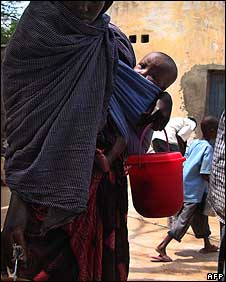 "A Somali woman holds a child as she and others receive food at an aid distribution center in the outskirts of Somalia""s capital, Mogadishu on July 21, 2008"