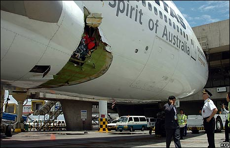 Qantas pilot Capt John Francis Bartels (R) looks at the hole in his plane at Manila airport