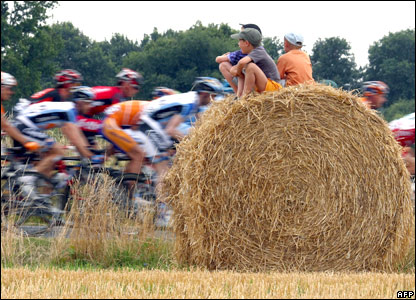 Three children sit on a roll of hay during the 19th stage of the Tour