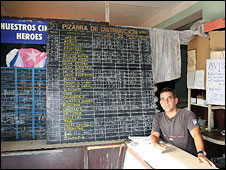 Shop with blackboard listing prices of goods brought with ration book