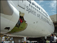 Staff inspect damage under the aircraft