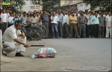 A policeman inspects a sack near the site of an explosion