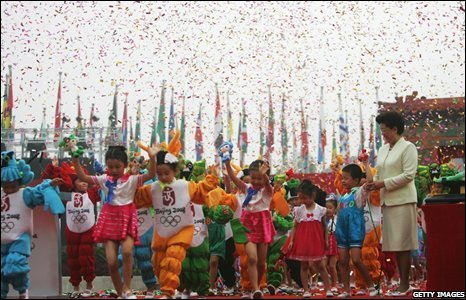 Chinese children perform as the Village Mayor Chen Zhili looks o