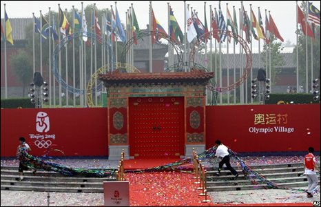 Chinese staff clear tinsel from the stage used during the opening ceremony