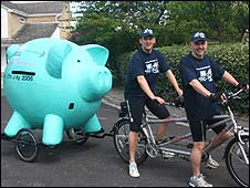 Two cyclists on tandem tow giant pig for charity