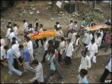Relatives and friends carry two bodies of blast victims for cremation in Ahmedabad
