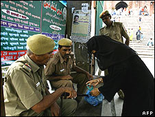 Police check a woman's bag in New Delhi 27 July