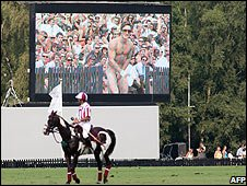 A polo player on a horse and a naked man on a big screen