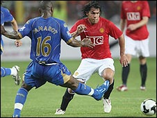 Man Utd striker Carlos Tevez (right) is closed down by Portsmouth defender Noe Pamarot in Nigeria