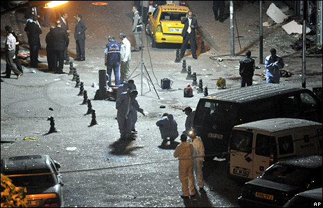 Police inspect the scene of one of the bombings