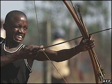 Kenyan man firing a bow and arrow