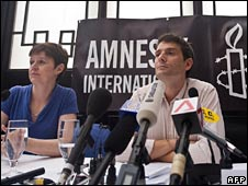 Amnesty International (AI) representatives Roseann Rife (L) and Mark Allison speak at a news conference in Hong Kong on Monday