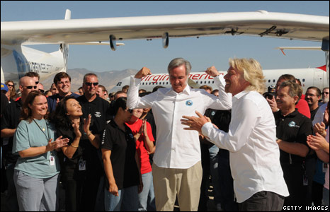 Richard Branson (R) and Burt Rutan joke with team members during the official launch of Virgin Galactic's White Knight Two